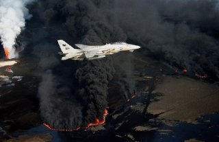 A U.S. Navy Grumman F-14A Tomcat from Fighter Squadron 114 (VF-114) Aardvarks flies over an oil well set ablaze by Iraqi troops during the 1991 Gulf War. VF-114 was assigned to Carrier Air Wing 11 (CVW-11) aboard the aircraft carrier USS Abraham Lincoln for a deployment to the Western Pacific and the Indian Ocean from 28 May to 25 November 1991. (Photo:Lt. Steve Gozzo, USN, via Wikimedia Commons)