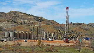 A workover rig stands over six pumping oil wells in the Little Missouri Grassland breaks north of Killdeer, N.D., in Dunn County in October 2015. (Forum News Service)