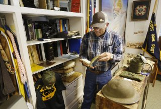 Everett DeWitt, volunteer curator of the Salt Creek Museum, flips through a book from the museum's collection Friday in Midwest.