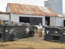 -In this file photo taken April 23, 2014, white-suited workers wearing respirators clean up the illegal filter sock dump in an abandoned gas station in Noonan, N.D.