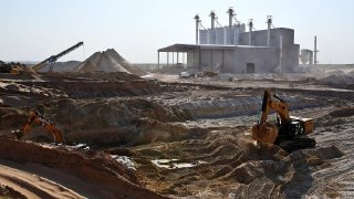 Heavy equipment digs sand from a pit at the HiCrush sand mine in Texas