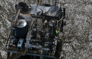 A worker stands on the oil and gas platform that burned in Lake Pontchartrain on Sunday night