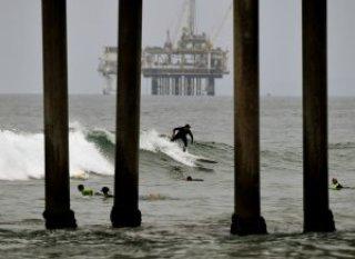 Surfers ride waves in front of an oil rig off Huntington Beach on July 31 2015