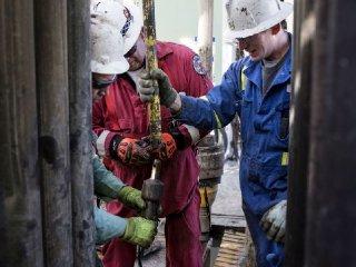 Precision Drilling oil rig operators install a bit guide on the floor of a Royal Dutch Shell Plc oil rig near Mentone Texas U.S.