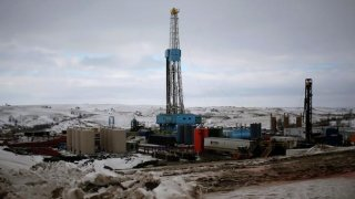 An oil derrick is seen at a fracking site for extracting oil outside of Williston North Dakota