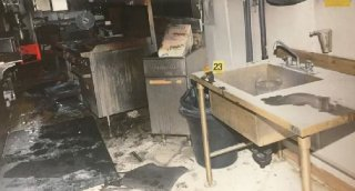 The burned out kitchen area of the work camp near Fox Creek Alta. where two employees were stabbed and murdered. A yellowhandled knife is police exhibit 23 found near the sink.
