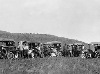A caravan of automobiles is on the road to Turner Valley in 1914.