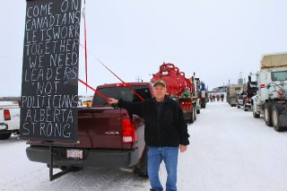 Semiretired machinist Laurie Gibson of Innisfail shows off his sign aimed at politicians.