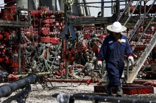 An employee walks by pressure pumps before hydraulic fracturing operations begin at a Chevron drilling site