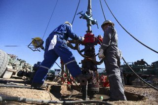 Oil field workers for Pioneer Natural Resources standing at a well that was being fracked on an oil field south of Midland, Texas.